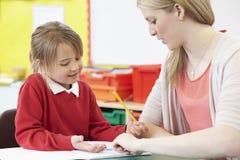 Lehrer Helping Female Pupil mit dem übenden Schreiben am Schreibtisch Lizenzfreie Stockfotos