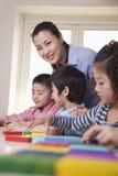 Lehrer Helping Her Students und Betrachten der Kamera lizenzfreies stockbild