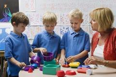 Lehrer Helping Little Boys bauen pädagogische Puzzlespiel-Spielwaren zusammen Stockfoto