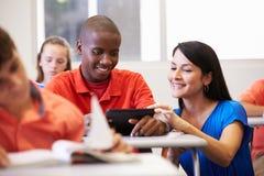 Lehrer-Helping Male High-Schüler In Classroom lizenzfreies stockbild
