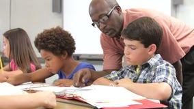 Lehrer Helping Male Pupil in der Klasse stock footage