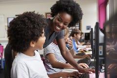 Lehrer-Helping Male Pupil-Linie von den hohen Schülern, die an den Schirmen in der Computer-Klasse arbeiten lizenzfreie stockbilder