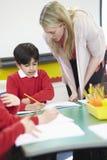 Lehrer Helping Male Pupil mit schriftlicher Arbeit am Schreibtisch Stockbild