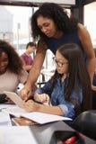 Lehrer hilft hohem Schüler mit der Technologie, vertikal stockbild