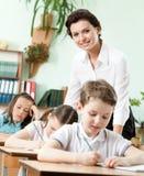 Lehrer hilft ihren Schülern, die Aufgabe zu tun Stockbild