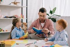 Lehrer im Brillenlesebuch zu den Kindern bei Tisch lizenzfreie stockbilder