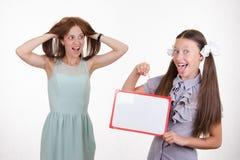 Lehrer im Horror, der den Studenten mit einem Zeichen betrachtet Stockfotografie