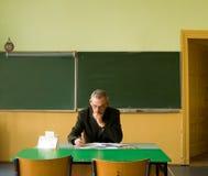 Lehrer im leeren Klassenzimmer Stockfotografie