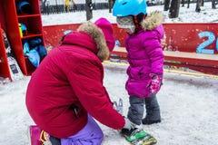 Lehrer knöpft Befestigung auf einem Snowboard Stockbild