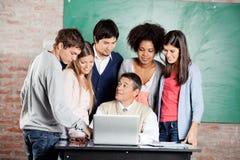 Lehrer-With Laptop Explaining-Lektion zu den Studenten Stockfotografie