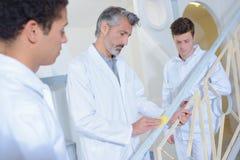 Lehrer, lehrlingen zeigend, wie man Metall für das Malen vorbereitet lizenzfreie stockfotos