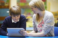 Lehrer With Male Pupil, das Digital-Tablet im Klassenzimmer verwendet Stockbild