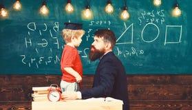 Lehrer mit Bart, Vater unterrichtet kleinen Sohn im Klassenzimmer, Tafel auf Hintergrund Junge, Kind im graduierten Kappenspiel stockfoto