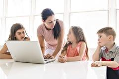 Lehrer mit einer Gruppe Schulkindern mit Laptop auf der Front stockbilder