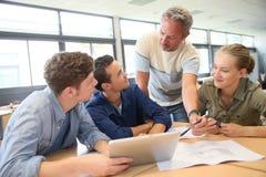 Lehrer mit Gruppe Studenten in der Schule Stockbilder