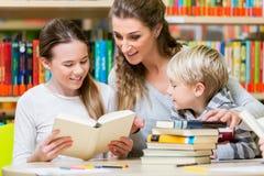 Lehrer mit ihrer Klasse, welche die Bibliothekslesebücher besucht stockbilder