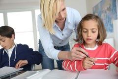 Lehrer mit Kindern an der Schule Stockbild