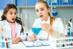 Lehrer mit kleinem Kind in Schullaborunerwartetem Ergebnis lizenzfreie stockbilder
