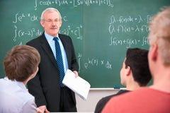 Lehrer mit Kursteilnehmern im Klassenzimmer stockbilder