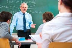 Lehrer mit Kursteilnehmern im Klassenzimmer Stockfotografie