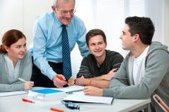 Lehrer mit Kursteilnehmern im Klassenzimmer stockfoto