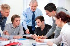 Lehrer mit School-Kursteilnehmern Lizenzfreie Stockbilder