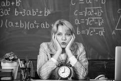 Lehrer mit Wecker an der Tafel Zeit Frau im Klassenzimmer Zur?ck zu Schule Lehrertag Studie und Bildung stockfoto
