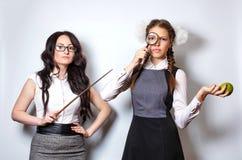 Lehrer mit Zeiger Schulmädchen mit Lupe und Apfel Stockbilder