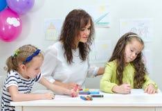 Lehrer mit zwei Mädchen Stockfotos