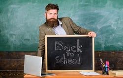 Lehrer- oder Erzieherwillkommensaufschrift zur?ck zu Schule Erfahrener Erzieher des Lehrers begrüßt neue Eingetragene, um anzufan lizenzfreie stockfotos
