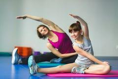 Lehrer oder Mutter mit der Tochter, die gymnastische Übungen tut Lizenzfreies Stockbild