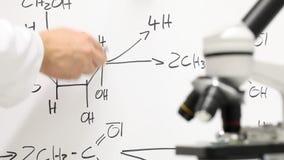 Lehrer oder Wissenschaftler, die chemischen Prozess auf whiteboard erklären stock footage