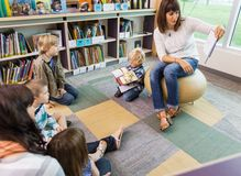 Lehrer-Reading Book To-Kinder in der Bibliothek Lizenzfreie Stockfotos