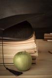 Lehrer-Schreibtisch mit den Büchern gestapelt, Doktorhut, Apple und Chalkb Stockfotografie