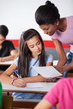Lehrer-Showing Paper To-Frau-Hochschulstudent Lizenzfreie Stockbilder