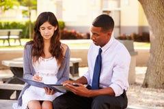 Lehrer-Sitting Outdoors Helping-Studentin With Work stockfotografie