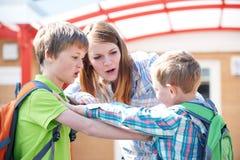 Lehrer Stopping Two Boys, das im Spielplatz kämpft Stockbild