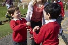 Lehrer Stopping Two Boys, das im Spielplatz kämpft Stockfotografie