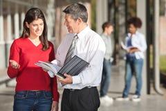 Lehrer And Student Discussing über Buch auf dem Campus Lizenzfreie Stockbilder