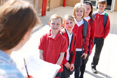 Lehrer Taking School Register im Spielplatz Stockfoto