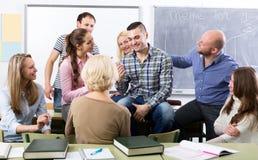 Lehrer und glückliche erwachsene Studenten Stockfotos