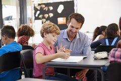 Lehrer und junger Schuljunge, die Notizbuch in der Klasse betrachten stockfotos
