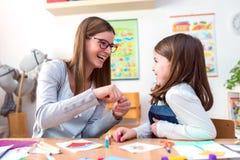 Lehrer und Kind, die Spaß und kreative Zeit zusammen haben Lizenzfreie Stockfotografie