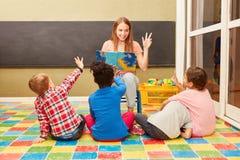 Lehrer und Kinder genießen, laut zu lesen stockbild