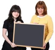 Lehrer und Kursteilnehmer mit unbelegtem Zeichen Lizenzfreie Stockfotos