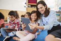 Lehrer und Mädchen in der grundlegenden Klasse unter Verwendung der Tablet-Computer stockbild