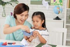 Lehrer und Mädchen, die Origami machen stockbild