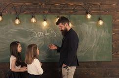Lehrer- und Mädchenschüler im Klassenzimmer nahe Tafel Neugieriger starker Kinderhörender Lehrer mit Aufmerksamkeit lizenzfreie stockfotos