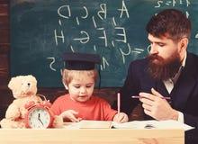 Lehrer und Schüler in der Doktorhut, Tafel auf Hintergrund Kind studiert mit dem Lehrer und hört mit Aufmerksamkeit lizenzfreie stockbilder