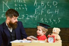 Lehrer und Schüler in der Doktorhut, Tafel auf Hintergrund Scherzen Sie glückliche Studien einzeln mit Lehrer, zu Hause stockbilder